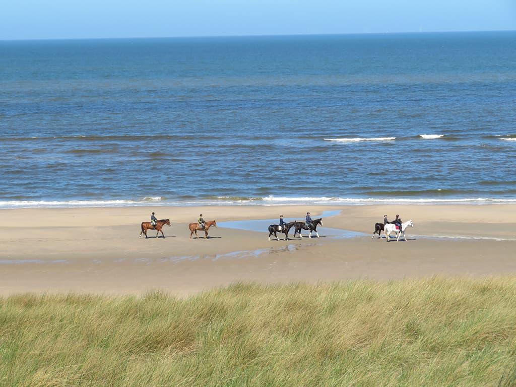 Nederlands Kustpad - ruiters op het strand